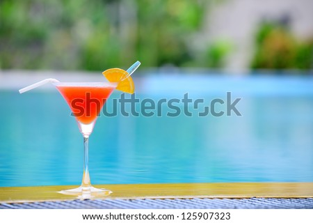 Cocktail at the edge of the swimming pool. Red cocktail with an orange slice on the background of the swimming pool