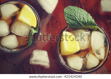 Cocktail Cuba Libre with lime and Ice into the glass beaker closeup - stock photo