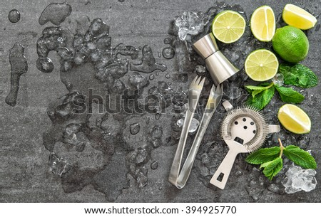 Cocktail drink making tools and ingredients with ice on dark stone background. Flat lay - stock photo