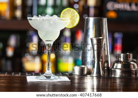 Cocktail garnished with lime standing on the bar counter. - stock photo