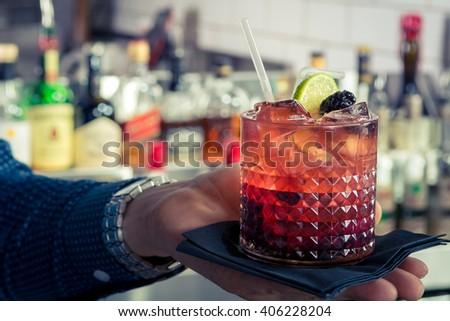 cocktail gin bramble blackberry lime blueberry crystal glass bar bartender hand - stock photo