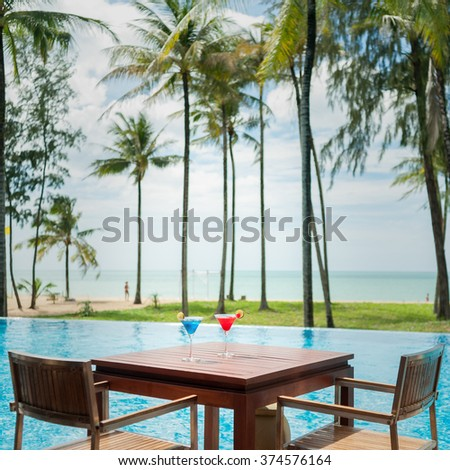 cocktail glass on wood table at pool with sea