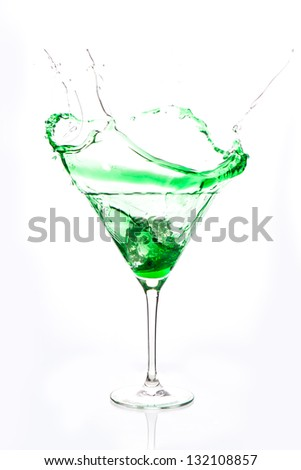 Cocktail glass with green alcohol splashing on white background