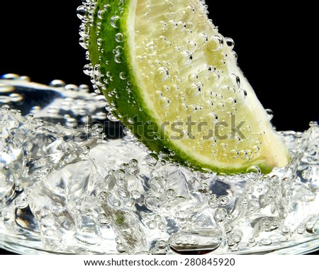 Cocktail glass with lime wedge and ice cubes isolated on white background  - stock photo