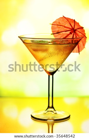 Cocktail glass with umbrella and holiday lights in the background - stock photo