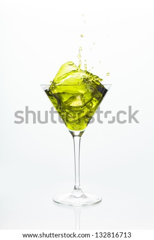 Cocktail glass with yellow alcohol on white background
