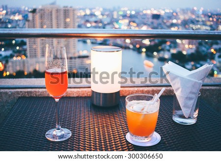 Cocktail glasses with candle light in rooftop bar against city view - stock photo