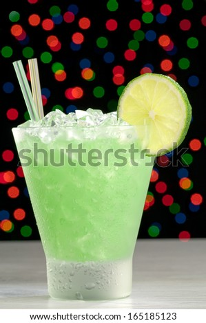 Cocktail in a frosted old fashioned glass with ice and lime on an unfocused color lights background