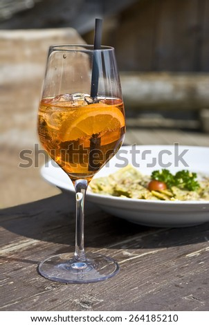 Cocktail in a glass with ice and a lemon against a dish with food. - stock photo