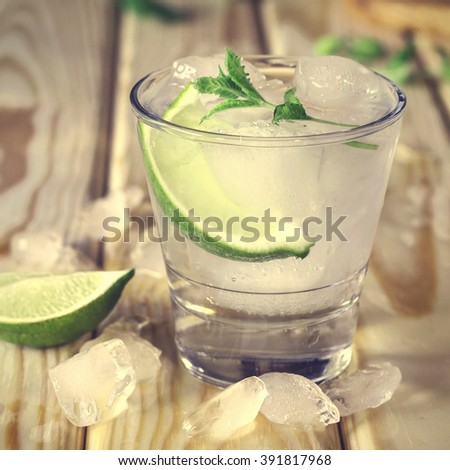 cocktail in a glass with ice. Vodka, vodka in a glass with ice, lime, a cocktail bar, alcohol, alcoholic beverage. Closeup . Square shot, - stock photo