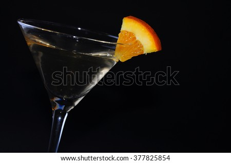 Cocktail in a martini glass garnished with an orange slice. Still life on black background. - stock photo