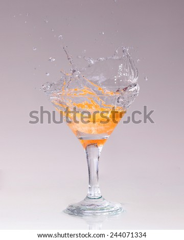 cocktail in a martini glass on a white background with fruit - stock photo