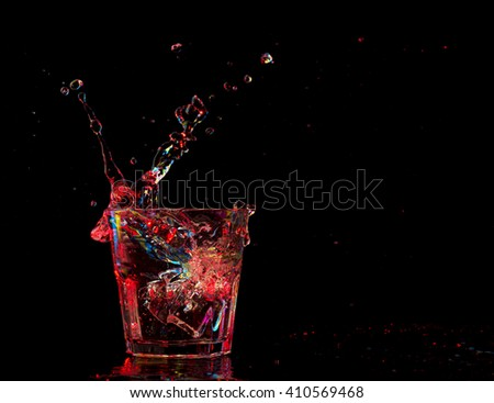 cocktail in glass with splashes on dark background. Party club entertainment. Mixed light. - stock photo