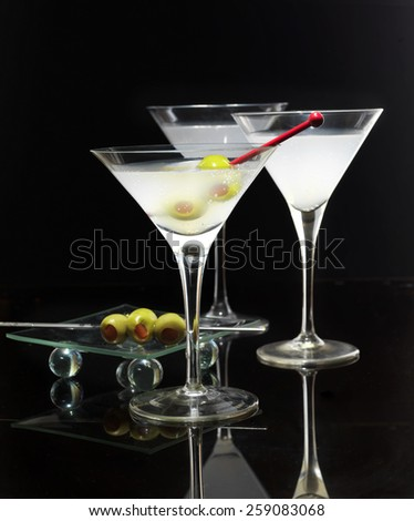 Cocktail in martini glasses with olives on black background - stock photo