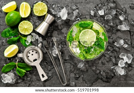 Cocktail juice with lime, mint and ice. Bar drink accessories on black table background. Alcoholic and nonalcoholic cold drinks