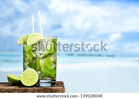 Cocktail mojito ice lemon straws in tropical beach Islands against a background - stock photo