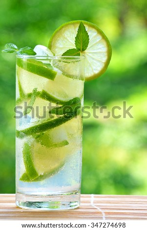 Cocktail mojito with lime and ice cubes on a blurred background.