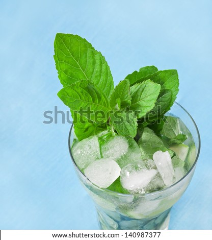 Cocktail mojito with mint leaf isolated on blue background