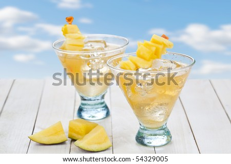 Cocktail of mango juice with ice cubes and pieces of fruit - stock photo