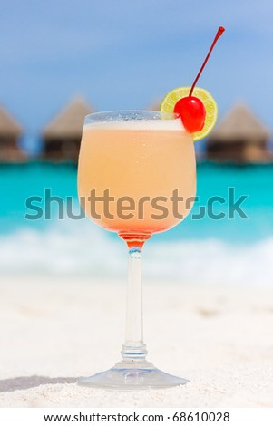 Cocktail on a beach with red cherry - stock photo