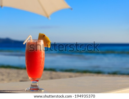cocktail on blue tropical beach at sunset - stock photo