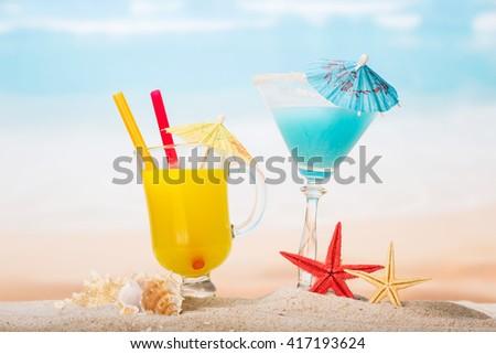 Cocktail, orange juice, starfish and shells on the beach. - stock photo