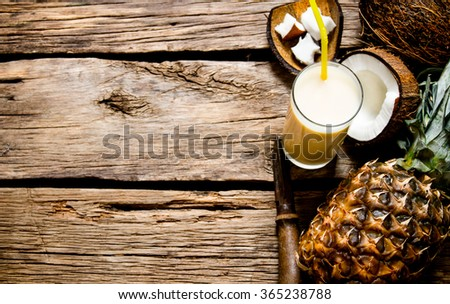 Cocktail pina colada. Fresh cocktail with coconut, rum and pineapple on a wooden table. Free space for text. - stock photo