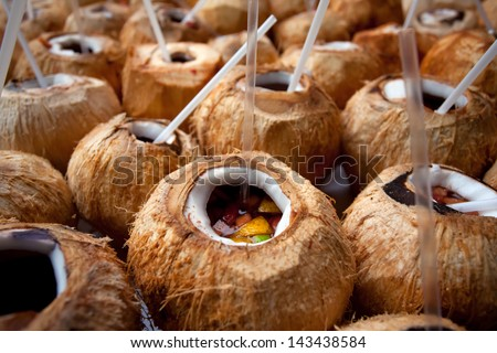 Cocktail served in coconuts with straws. Shallow depth of field. - stock photo