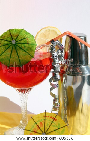 Cocktail shaker and red cocktail in tall glass with umbrella