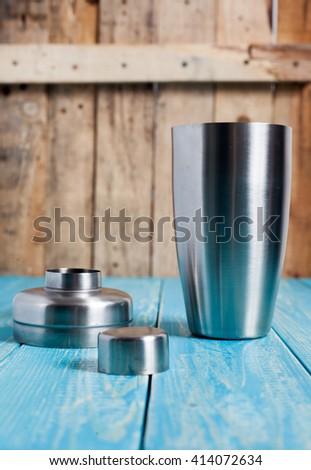 Cocktail shaker on bright aqua wood background - stock photo