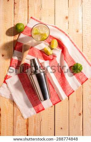 Cocktail shaker with an iced martini cocktail and fresh lemon and lime on a striped red and white napkin on a rustic wooden table outdoors in sunshine - stock photo