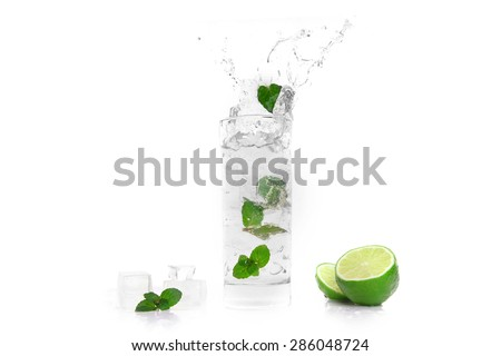 cocktail splashing into glass and cube of ice  - stock photo