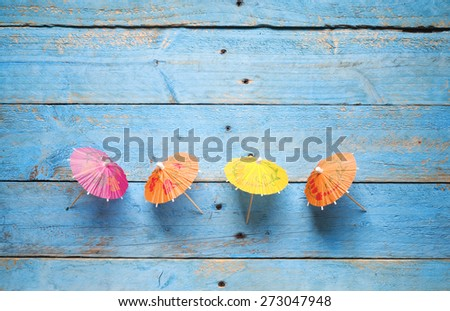 cocktail umbrellas, on blue planks background, free copy space - stock photo