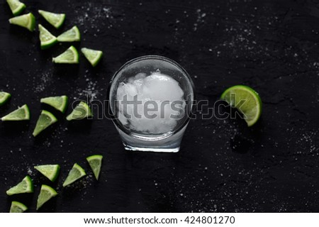 Cocktail vodka or gin with ice and slice lime on a dark background, top view with copy space - stock photo
