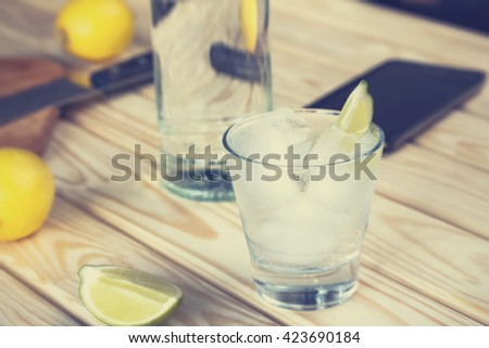 Cocktail vodka or gin with ice vintage. Closeup Selective focus, blur, background, vodka in a glass with ice, lime, a cocktail bar, alcohol, alcoholic beverage.  - stock photo