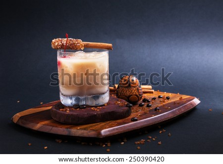 Cocktail/White russian  with  sugar cinnamon stick on wooden  in Black background - stock photo