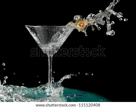 Cocktail with a olive splash in martini glass - stock photo