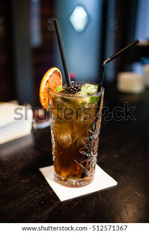 Cocktail with black straw in a bar.