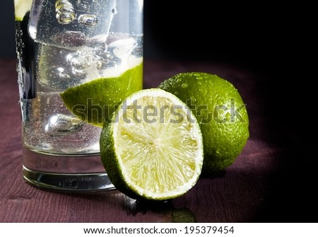 Cocktail with ice and lime slice isolated on wood table and space for text - stock photo