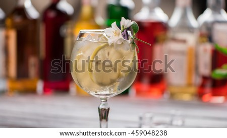 Cocktail with ice in wineglass. Flower and slice of lemon. Simple decorated cocktail. Tom collins served at club. - stock photo