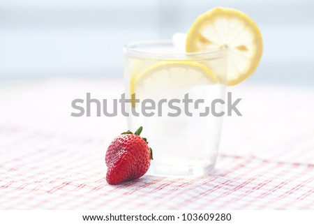 cocktail with ice, lemon and strawberry - stock photo