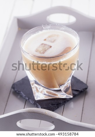 Cocktail with ice over tray, vertical image