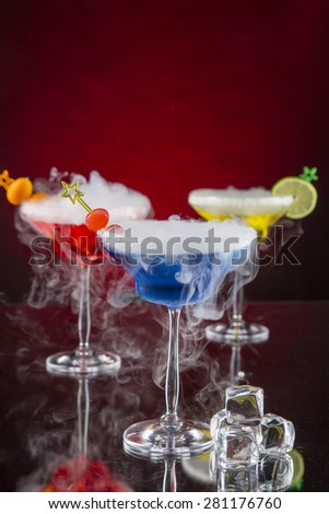 Cocktail with ice vapor on bar desk, close-up. - stock photo