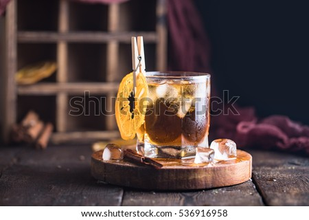 Cocktail with iced tea, whiskey, orange and ice in a glass on the wooden tray on the dark background