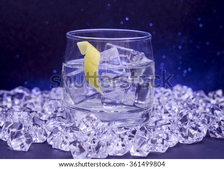 Cocktail with lemon twist surrounded by ice