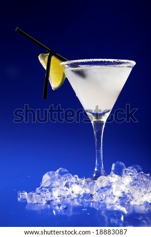cocktail with lime and ice on blue