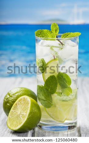 cocktail with lime and mint on a beach - stock photo