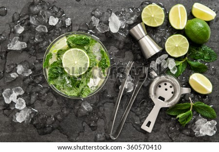 Cocktail with lime, mint and ice. Bar drink accessories on black table background. Top view. Selective focus - stock photo