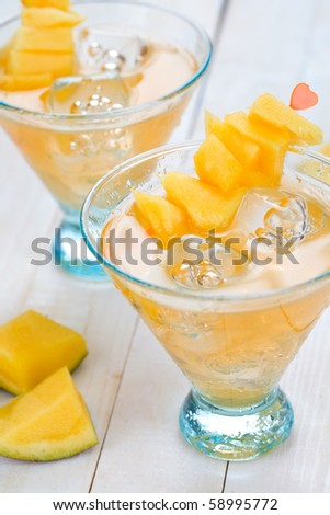 Cocktail with mango fruit on wooden table top