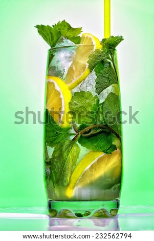 Cocktail with mint and lemon on the bar on the blur background. - stock photo
